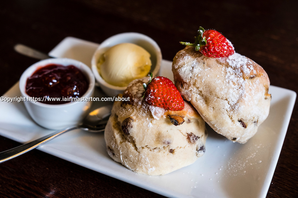 Detail of traditional fruit scones with butter and jam served as a high tea in a traditional English cafe in the United Kingdom