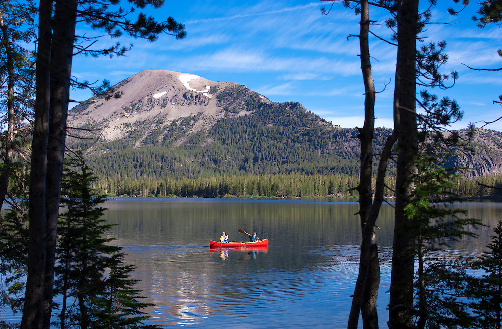 Boy and girl paddling red canoe on Lake Mary; Mammoth Lakes, Eastern Sierra Nevada Mountain, California.