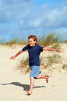 Young boy running down sand dune on beach