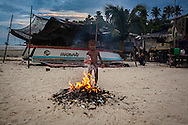 A Bajau child throws a bottle of Coke in the fire where every night the garbage is removed