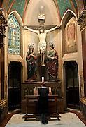 A pilgrim prays in front of a crucifix in Rome. (Sam Lucero photo)
