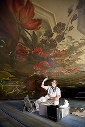 "© Licensed to London News Pictures. 04/03/2013. London, UK. On top of a scaffolding tower at around 40 feet in the air, restoration expert Francesco Rosellini works on the ceiling of the 'Painted Hall' at Greenwich Old Naval College in London today (04/03/2013). The conservation work, paid for by the Heritage Lottery Fund (HLF), is the 10th time the Painted Hall (often described as ""finest dining hall in Europe"") will have been restored since its completion in 1784 and will have taken around five months to complete when the hall is unveiled to the public in May of this year. Photo credit: Matt Cetti-Roberts/LNP"