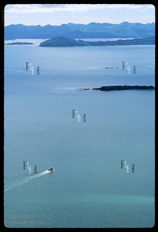 Tugboat cruises across Chiniak Bay toward distant mountains on a sunny August day; Kodiak. Alaska