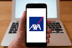 Using iPhone smartphone to display logo of AXA the French multinational insurance firm