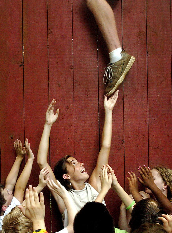 A group of campers participate in a team building exercise at Camp Kum-ba-yah in Lynchburg, Va. by attempting to lift each team member over a climbing wall.