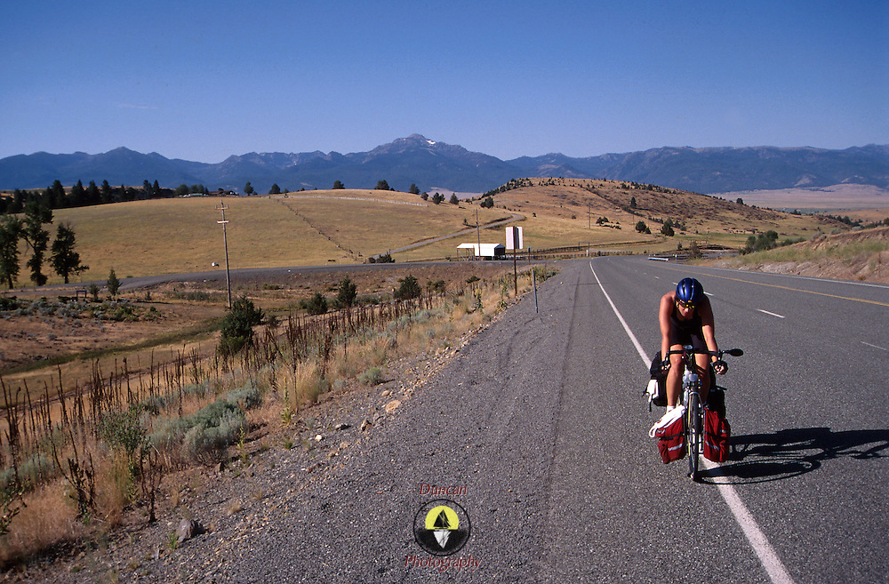 Emily J. Biss rides uphill away from the rockies in the dry lowlands of Central Colorado while Bicycling across the USA . .Photo by Roger S. Duncan.  ...
