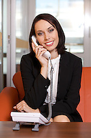 Businesswoman conversing on landline phone, portrait
