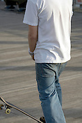 side view of a teenage boy with his skateboard