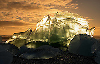 On Jökulsárlón Beach in Iceland the massive clumps of ice form some amazing shapes, letting you imagination run wild can lead you astray.  As the sun was dipping below the horizon the sky and lit up the sky, and at the same time throwing up some amazing backlighting on this large piece of ice.  At this time i found my mind wondering towards the  Supermans Fortress of Solitude, from movies gone by...