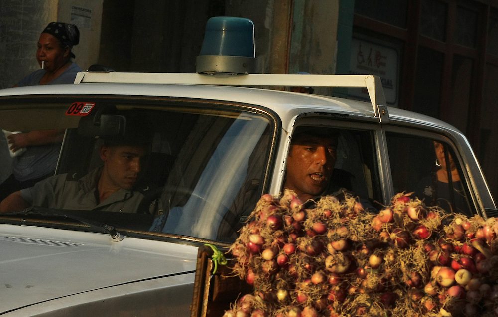 Cuban police officers inspect produce at a local food stand in Old Havana, Cuba.<br /> There is a huge police presence in Cuba with postings on the street corners of all major cities enforce traffic laws and inspect vehicles.