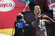 A young man with a teddy bear on top of his head dances to the music of loud speakers mounted on a moving trailer to amuse the crowd during the parade held on the occasion of the annual Oguaa Fetu Afahye Festival in Cape Coast, Ghana on Saturday September 6, 2008.