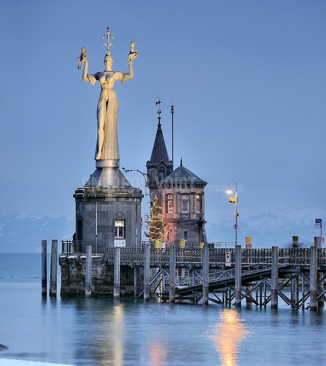 Die Imperia, eine Statue im Hafen von Konstanz am Bodensee, vor den Bergen der Schweiz. Entworfen und ausgeführt wurde sie von dem Bildhauer Peter Lenk und 1993 aufgestellt. Die Figur ist aus Beton gegossen, neun Meter hoch, 18 Tonnen schwer und dreht sich mit Hilfe eines Rundtisches innerhalb von drei Minuten einmal um die eigene Achse. In ihrem Sockel ist eine Pegelmessstation integriert.