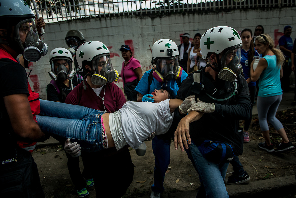 """CARACAS, VENEZUELA - JUNE 3, 2017:  Medical students evacuate a woman that was having multiple, uncontrollable seizures and drifting in and out of consciousness after being heavily tear gassed by security forces during a peaceful protest.  Hundreds of medical students volunteer on the front line of clashes as """"Green Helmets"""" - first responders that evacuate and give first aid to injured protesters.  Many young medical students are angry about the poor state of the public healthcare system.  Over 85 percent of medicines are either impossible, or very difficult to find in Venezuela.  Public hospitals face shortages of even the most basic supplies, like gauze, latex gloves, syringes - even running water. Many say they see volunteering with the Green Helmets as using their talents to supporting the protest movement taking over the streets of Caracas. PHOTO: Meridith Kohut"""