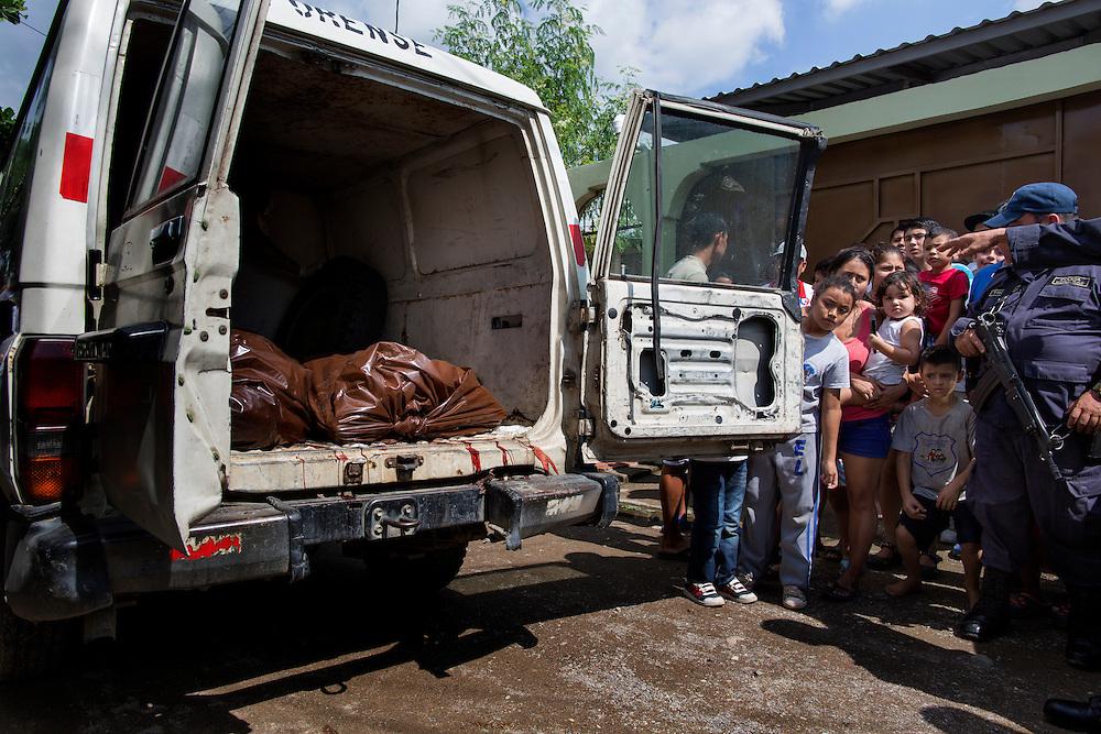San Pedro Sula, Honduras<br /> <br /> Trebarns pappan sk&ouml;ts ihj&auml;l n&auml;r han skulle bege sig fr&aring;n hemmet. <br /> Bilen som h&auml;mtar upp kropparna &auml;r gammal, sliten och blodig. I bilen f&auml;rdas r&auml;ttsl&auml;karen och tv&aring; b&auml;rare. Kropparna tas till b&aring;rhuset f&ouml;r obduktion.<br /> <br /> Photo: Niclas Hammarstr&ouml;m