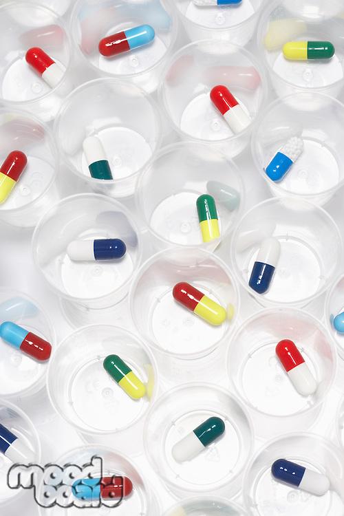 Capsule pills in plastic cups