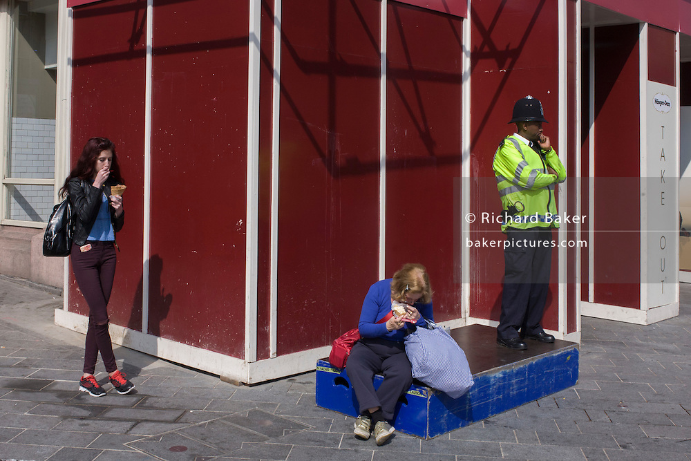 Eating women and a Met Police officer on a street corner in Leicester Square in central London.