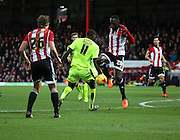 Brentford midfielder Toumani Diagouraga dispossesing Hudderfield Town striker Ishmael Miller after a Hudderfield Town chance during the Sky Bet Championship match between Brentford and Huddersfield Town at Griffin Park, London, England on 19 December 2015. Photo by Matthew Redman.