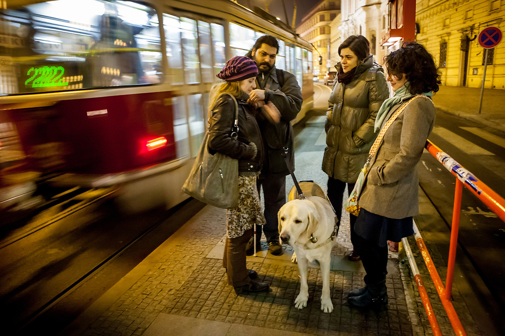 """Mario waiting with friends and his guiding dog """"Harley"""" for a tramway in the center of Prague. Mario is a well known blind Roma musician originally from Slovakia living since he finished his studies in Prague, Czech Republic. Beside being a very talented multi-instrumentalist working as a professional musician he is also experimenting with photography as a another way to express himself."""
