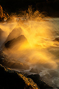 At high tide, Pacific Ocean waves crash into the rocks of the Marin Headlands in the Golden Gate National Recreation Area near San Francisco, California. Spray from the crashing waves is turned golden by the light of the setting sun.