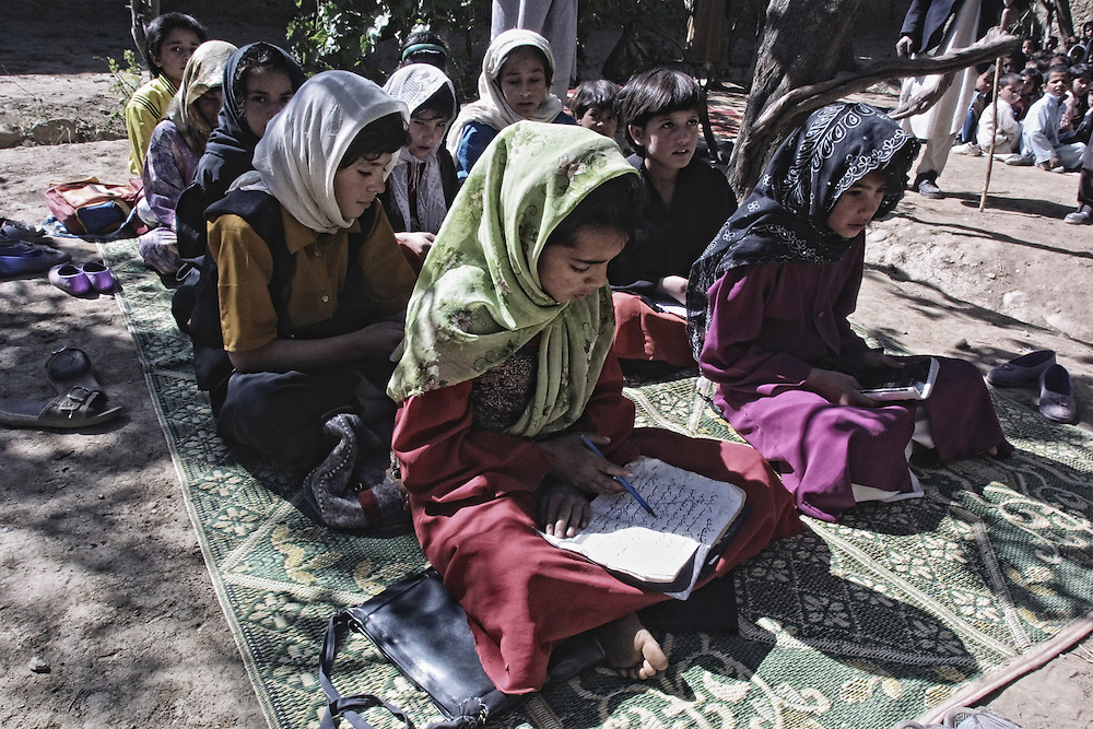 20011013-GULBAHAR, AFGHANISTAN: Afghan children listen a lesson at a school in Gulbahar, some 30 km from Kabul, 13 October 2001. US warplanes and missiles bombarded Afghan airbases and military camps on Saturday, 13 October 2001, but frustrated opposition forces claimed Washington was not targeting frontline Taliban positions.