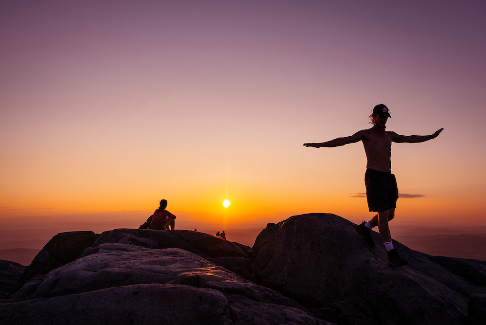 Playing airplane on a mountain summit in New Hampshire at sunset