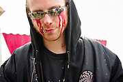 A portrait of a man wearing sunglasses and red face paint, Boomtown, Matterley Estate, Alresford Road, near Winchester, Hampshire, UK, August, 2010