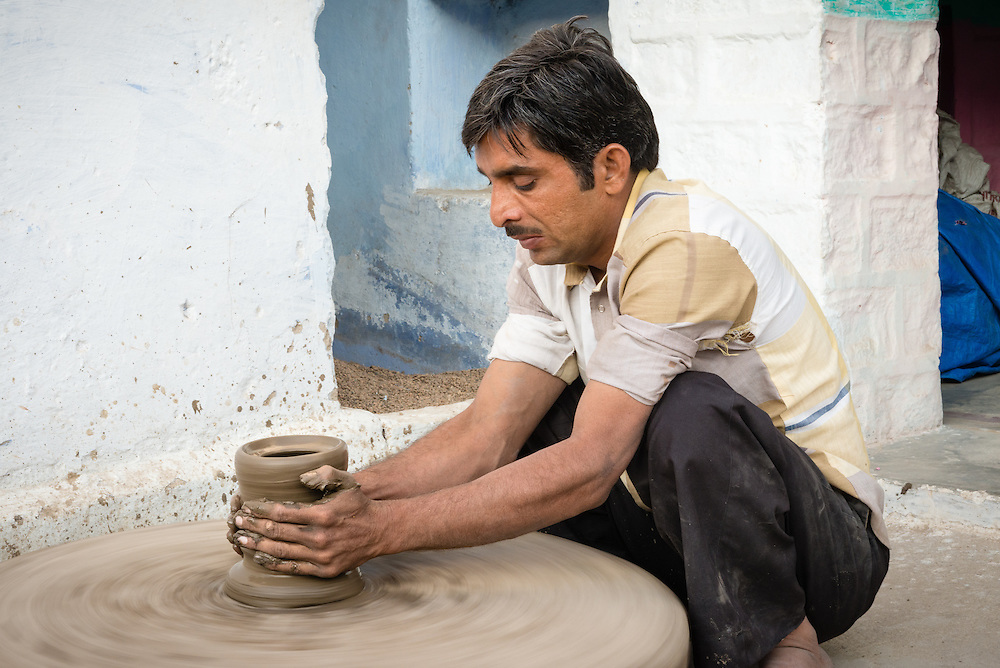 Man making clay bowl on potting wheel in village of Chandaleo