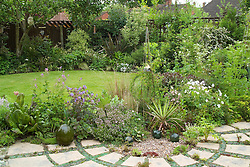 View of small garden with intersecting cirles of lawn and paving. Patio decorated with plants and sunken upturned bottles. Design: David Chase / Alison Hoghton
