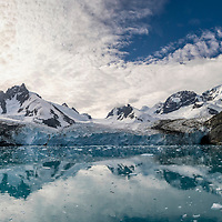 Reflection of the landscape with the Risting Glacier in Dygalski Fjord on South Georgia Island.