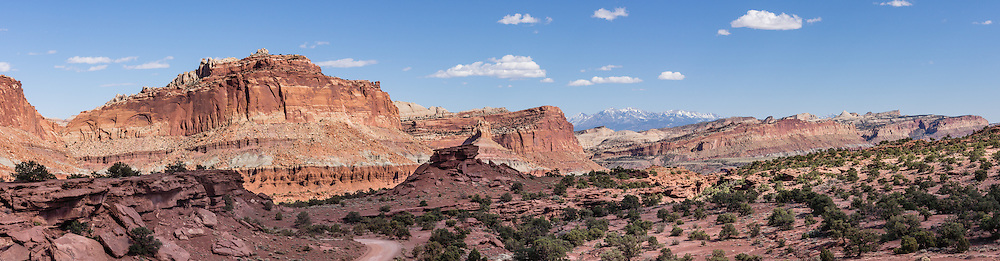 Capitol Reef National Park is centered upon the 100-mile-long Waterpocket Fold, the steep eastern limb of the Circle Cliffs Uplift, formed in Late Cretaceous time, during the Laramide Orogeny. Pressure caused by the subduction of the Farallon Plate beneath the North American Plate along the west coast caused several huge folds like this in southeast Utah, USA. Steeply tilted Triassic and Jurassic rocks form the hogbacks of the Waterpocket Fold and Capitol Reef, which is built of dark-red dune-formed Wingate Sandstone, plus thinly bedded river deposits of the Kayenta Formation, crested by the massive, white, dune-formed Navajo Sandstone. This panorama was stitched from 5 overlapping photos.
