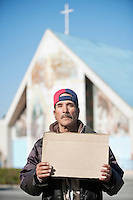 Portrait of homeless man with sign in front of church
