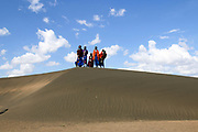 A group of Maasai tribespeople stand on a distant hill with a blue sky background