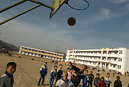 Children playing basket ball in their high school courtyard