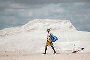 A woman walks towards the shore to work on the salt extraction at the Lac Rose near Dakar, Senegal, on Tuesday, July 26, 2016. *** Second Sentence *** Photographer: Xaume Olleros/Bloomberg