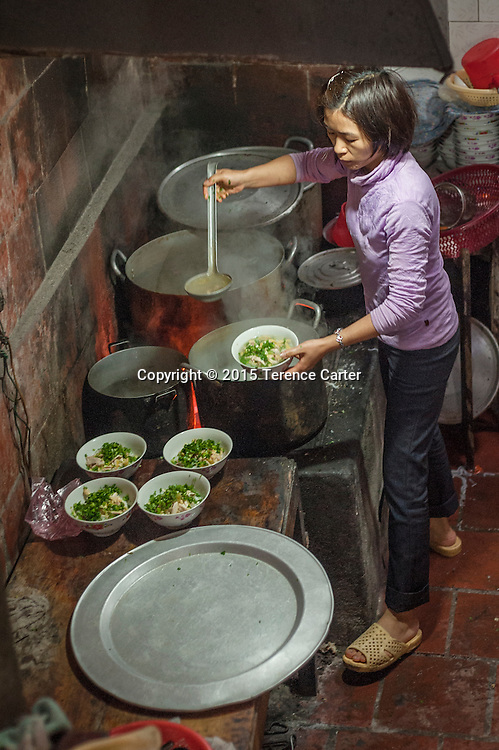 A vendor plates up bowls of Phở, the classic Vietnamese soup in the markets in Sapa, VIetnam.