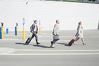 Side view of businesspeople with luggage walking on street