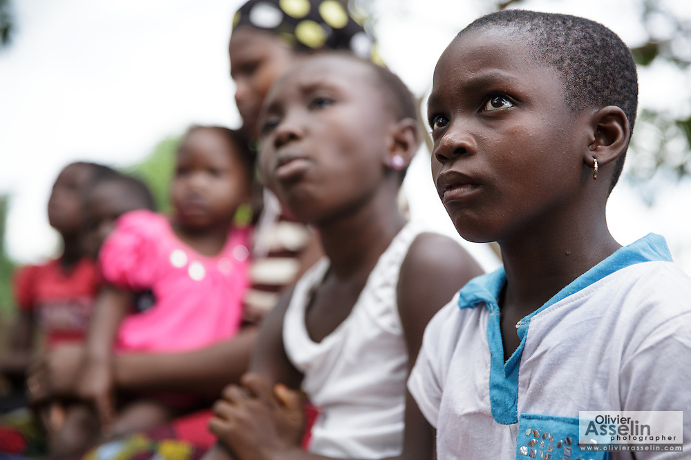 Children listen while a staff member from UNICEF partner OIS Arique speaks about female genital mutilation during a community gathering in the town of Katiola, Cote d'Ivoire on Saturday July 13, 2013.