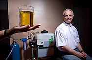 Chris Elvey, a director of EcoTech, a company based in Bamber Bridge, Lancashire, seated at 100-litre capacity separating system examining a sample of biodiesel produced at his company's plant. The firm takes used commercial vegetable oil and separates it into glycerol and biodiesel, the latter of which can be used in domestic and commercial vehicles. EcoTech was established three years ago and now produces around 7000 litres per week.