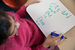 Girl sitting at desk in classroom practising writing skills,
