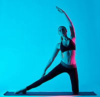 one caucasian woman exercising Parighasana gate pose yoga exercices  in silhouette studio isolated on blue background