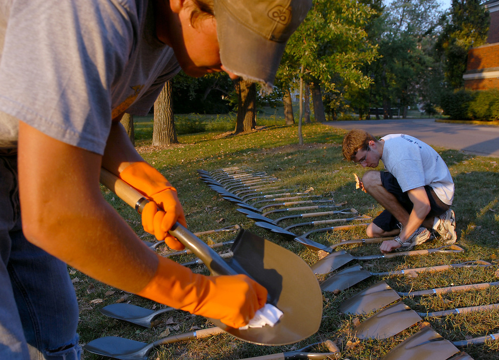 Patrick Karnes (left), a senior in the Russ College of Engineering and Technology, and Patrick Fahey, junior, wipe down shovels in the grass behind the Stocker Center on West Green Thursday as they were being prepped for gold paint for the groundbreaking ceremony for the new Integrated Learning and Research Facility on September 29th. .Ty Wright photo
