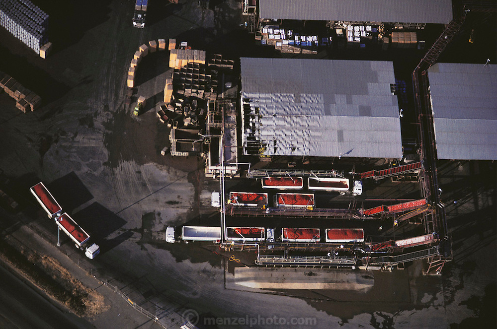 Aerial photograph of the production facility for freshly harvested tomatoes.  Seen are truck trailers of just harvested tomatoes. Tomato cannery. San Joaquin Valley, California.