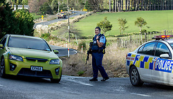 Armed police man a road block on Mt Tiger Road after two women were found dead and a man was taken to hospital with gunshot wounds, with the house at the centre of attention now having been engulfed in fire, Whangarei, New Zealand, Wednesday, July 26, 2017. Credit:SMPA / Malcolm Pullman   **NO ARCHIVING**