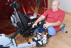 Man with prosthetic limb using a rowing machine at the gym,