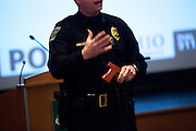 Ohio University Police Officer Captain Brian Kapple demonstrates with a fake gun about what to do during an active shooter situation in Athens, Ohio on Monday, February 18, 2013. Photo by Chris Franz