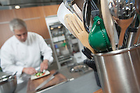 Mid- adult chef working with utensil holder in foreground