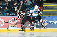 KELOWNA, CANADA, JANUARY 1: Cody Sylvester #16 of the Calgary hit men checks Carter Rigby #11 of the Kelowna Rockets into the boards as the Calgary Hitmen visit the Kelowna Rockets on January 1, 2012 at Prospera Place in Kelowna, British Columbia, Canada (Photo by Marissa Baecker/Getty Images) *** Local Caption ***