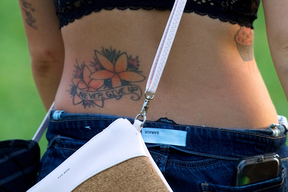 "A reveler with a tattoo stating ""NEVER GIVE UP"" walks through the concert grounds on the second day of the Firefly Music Festival in Dover, Delaware U.S., June 15, 2018.  REUTERS/Mark Makela"