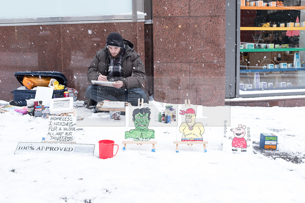 """© Licensed to London News Pictures. 28/02/2018. <br /> <br /> A homeless artist working in the snow in Glasgow, Scotland during snow storm """"Beast from the East"""" on 28th February 2018.<br /> <br /> Photo credit should read Max Bryan/LNP"""