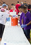Middletown, New York - Volunteer workers fill water near the finish line before the start of the 16th annual Ruthie Dino-Marshall 5K Run/Walk put on by the Middletown YMCA on Sunday, June 10, 2012.
